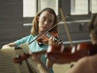 Saoirse Ronan mentre si esercita a suonare il violino con il suo quartetto d'archi